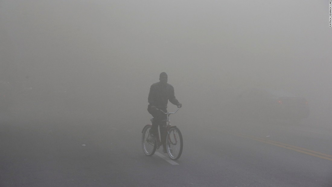A man rides a bicycle through heavy smoke emitting from a nearby store on fire April 27.