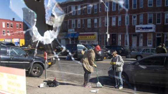 Two women sweep up the streets in Baltimore -- reflected in the broken window of a storefront on April 28. See more photos of the cleanup efforts.