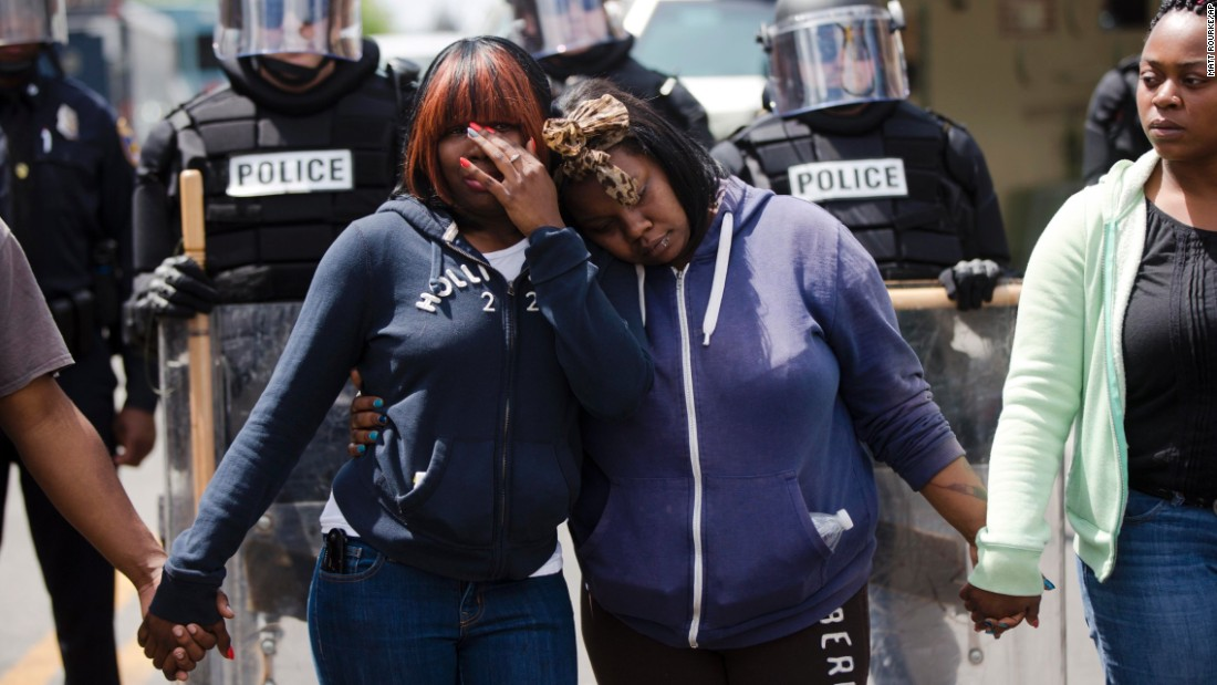 "Jerrie Mckenny, left, and her sister Tia Sexton embrace as demonstrators hold hands and sing the hymn ""Amazing Grace"" in Baltimore on April 28."