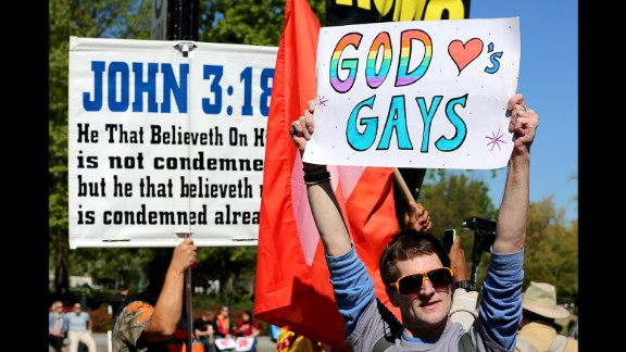 James Rowe holds a sign supporting gay marriage next to a group who are against it.