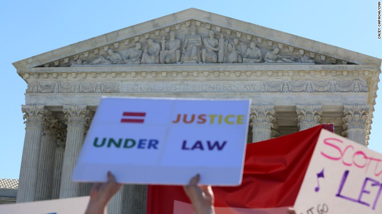 outside the supreme court of the united states people hold signs calling for