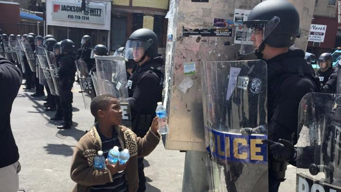 A boy in Baltimore offers water to a police officer on April 28.