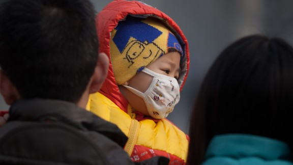 An infant wearing a mask was carried along a street in severe pollution in Beijing on January 12, 2013.