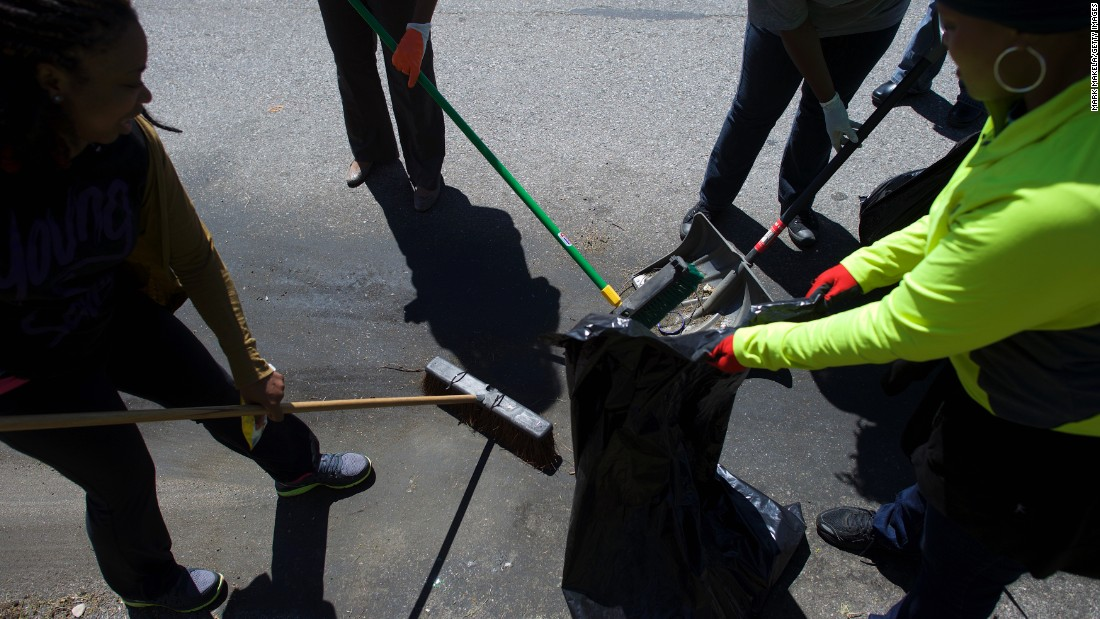 A neighborhood cleanup crew works to clear trash from the streets on April 28.