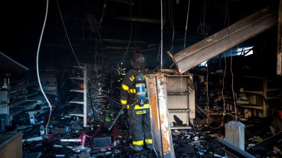 A Baltimore firefighter inspects a burned CVS store on April 28. About 200 businesses were lost in the riots.