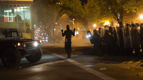 A community organizer later identified as Joseph Kent paces in front of riot police with his hands up during a curfew in Baltimore on Tuesday, April 28. Moments later, he was seen being arrested by police live on CNN. Kent