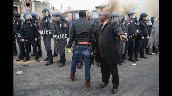 A man attempts to calm a fellow demonstrator as they face police in Baltimore in April 2015. Riots broke out after the funeral for Freddie Gray, who died of a severe spinal cord injury while in police custody. His death sparked protests in Baltimore and raised long-simmering tensions between police and residents.