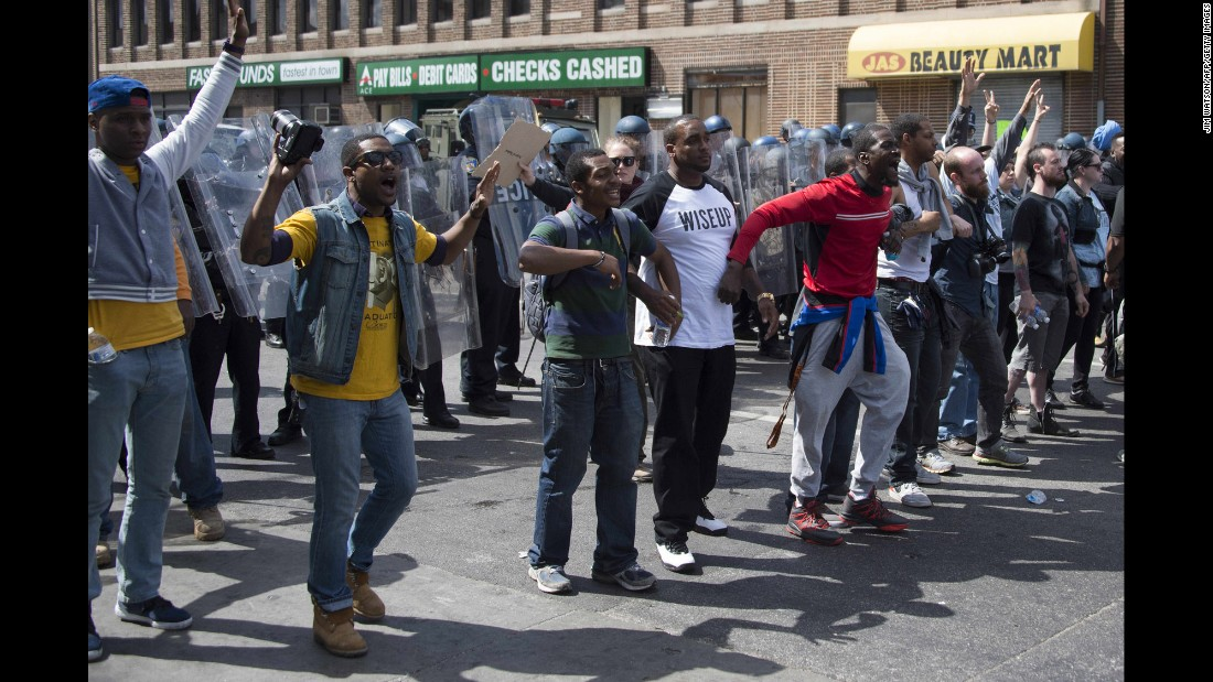 Demonstrators stand in front of a police line and call for peace after a bottle was thrown on April 28.