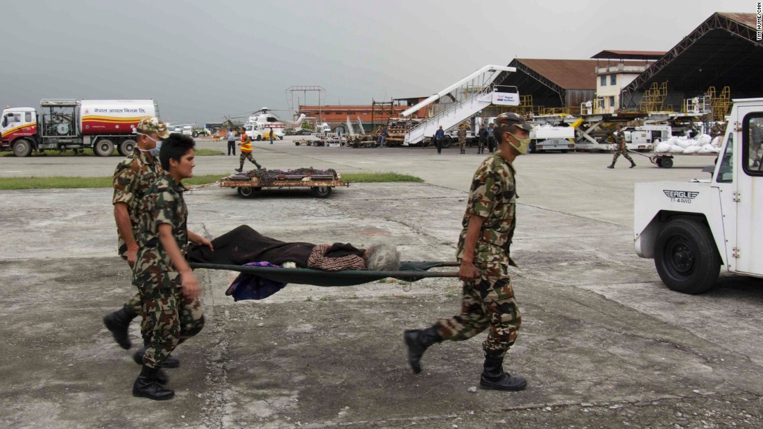 Soldiers carry a man from Melamchi who was injured in the Nepal quake through the air base in Kathmandu for medical treatment.
