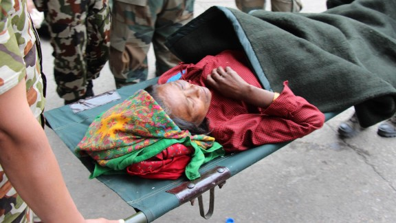 Forshani Tamang, whose children carried her for four hours from her village, Bachunde, to Malamchi for help, is picked up at the Kathmandu air base to be taken to hospital.