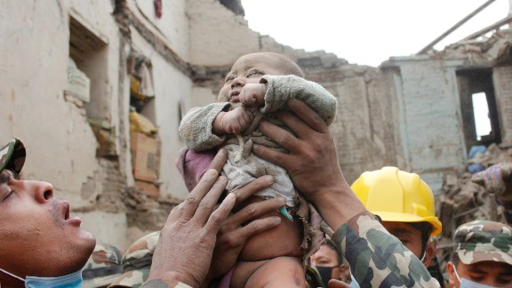 In this Sunday, April 26, 2015, photo taken by Amul Thapa and provided by KathmanduToday.com, four-month-old baby boy Sonit Awal is held up by Nepalese Army soldiers after being rescued from the rubble of his house in Bhaktapur, Nepal, after Saturday