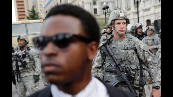 A member of the National Guard stands outside Baltimore City Hall as protesters gather on Wednesday, April 29.