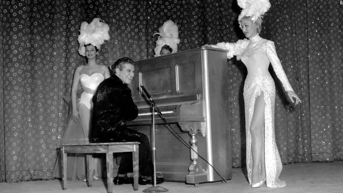 "Liberace's ""Piano Roll Blues"" helped roll out the carpet at the premiere of the Riviera in April 1955. Here, Liberace is shown in attire by Dior and with support from hotel chorus girls."