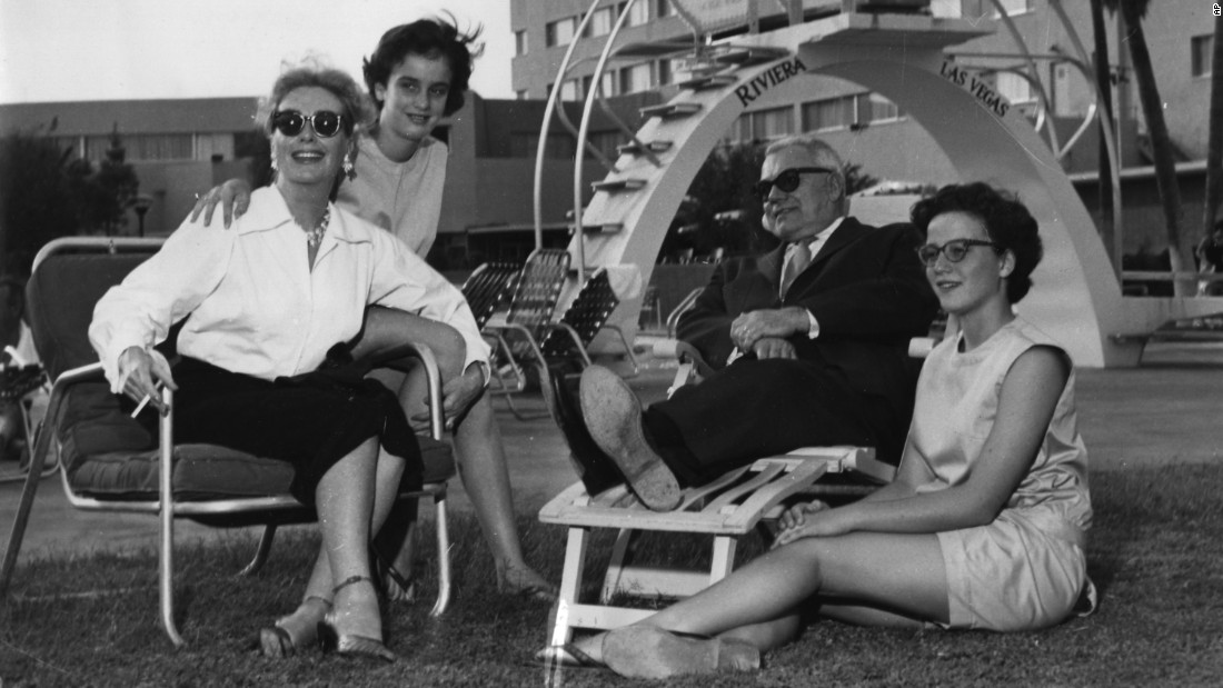 Actress Joan Crawford relaxes with her husband, Alfred Steele, and her twin daughters, Cathy and Cindy, at the Riviera's pool in October 1958.