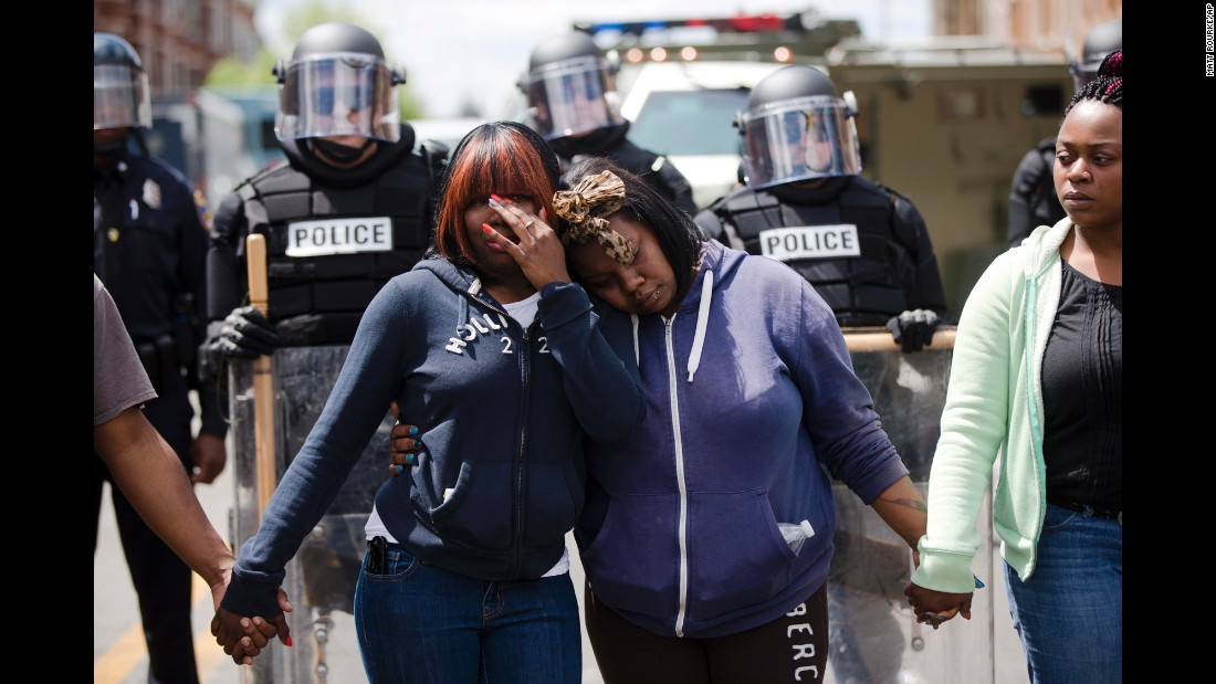 "Jerrie Mckenny, left, and her sister, Tia Sexton, embrace as people sing the hymn ""Amazing Grace"" on Tuesday, April 28, in Baltimore, in the <a href=""http://www.cnn.com/2015/04/23/us/gallery/freddie-gray-protest/index.html"" target=""_blank"">aftermath of rioting</a> following Monday's <a href=""http://www.cnn.com/2015/04/27/us/gallery/freddie-gray-funeral/index.html"">funeral for Freddie Gray</a>, who died in police custody. People in cities <a href=""http://www.cnn.com/2015/04/30/us/gallery/freddie-gray-protests-across-us/index.html"" target=""_blank"">across the United States</a> have shown their support for protesters in Baltimore since then."