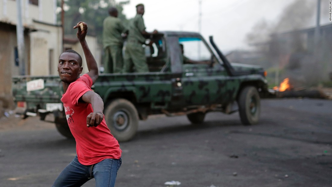 A demonstrator throws a stone at Burundi riot police on Wednesday, April 29, as a Burundi military truck drives by in Bujumbura. Protesters took to the streets again, angry over the Burundian president's bid for a third term in office.
