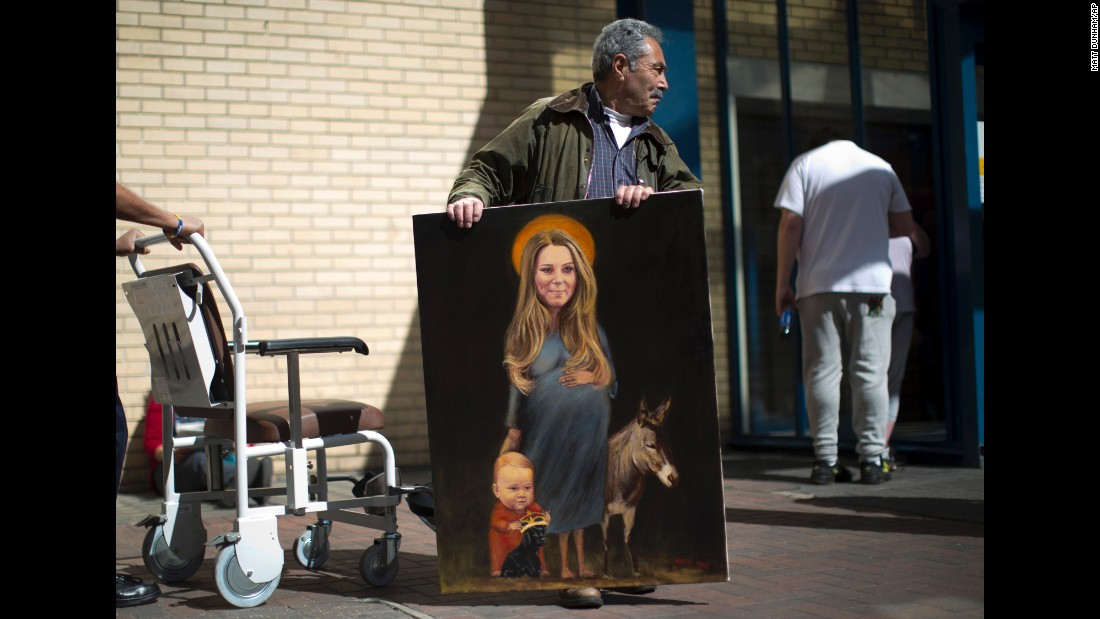 "Artist Kaya Mar poses for photographs on Monday, April 27, with his painting entitled ""Saint Kate"" across the street from St. Mary's Hospital in London, where Catherine, Duchess of Cambridge, is expected to give birth to her second child."