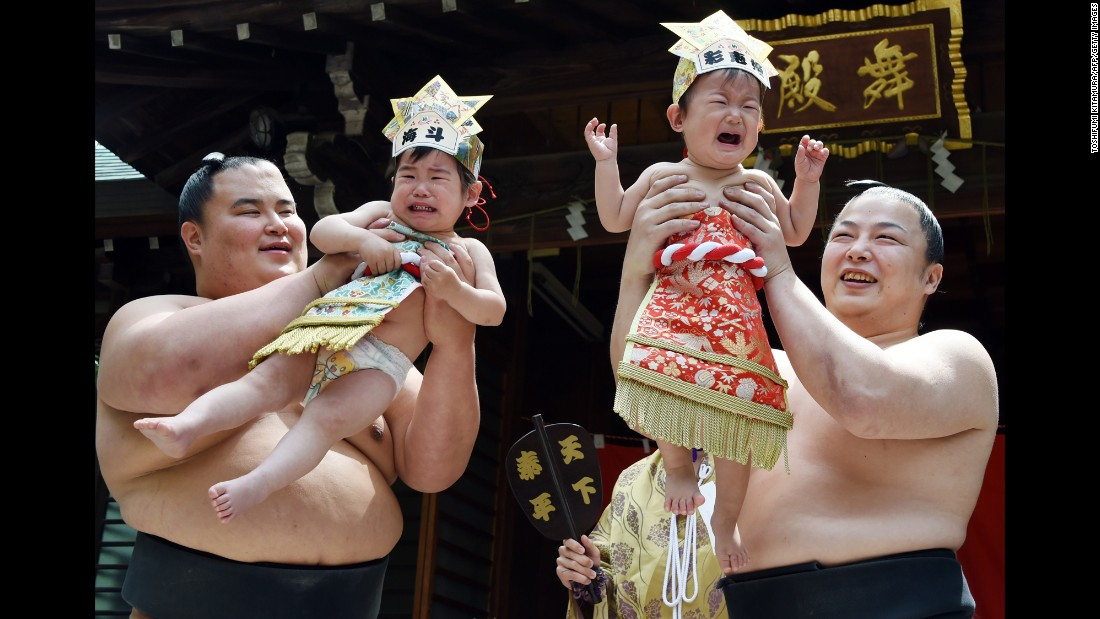"Sumo wrestlers from Onoe stable hold up crying babies during a ""Baby-cry Sumo"" event at the Yukigaya Hachiman shrine in Tokyo on Wednesday, April 29. Around 100 babies younger than a year old took part in the annual baby crying contest."