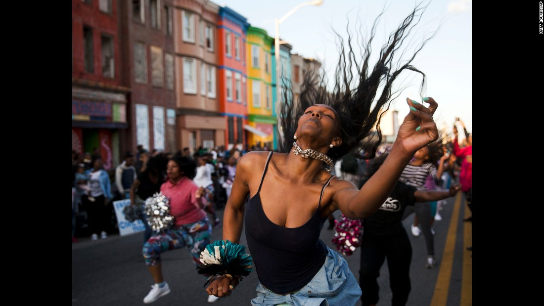 People dance in the street on Tuesday, April 28, in Baltimore. Maryland Gov. Larry Hogan declared a state of emergency and activated the National Guard on Monday night when protests turned into riots.