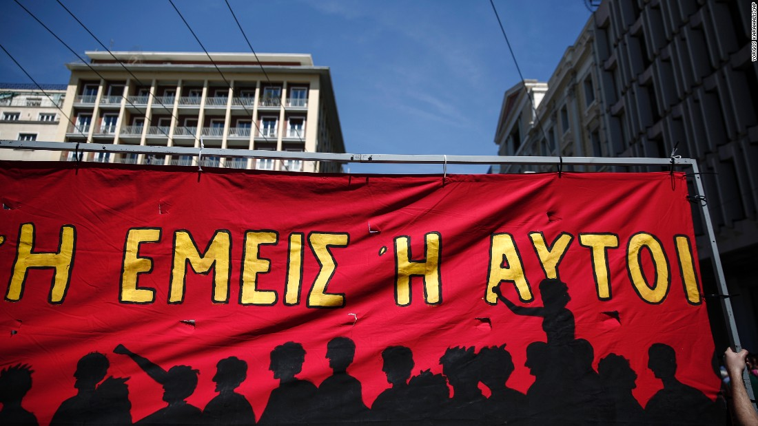 Protesters hold up a banner during a May Day rally in Athens, Greece.