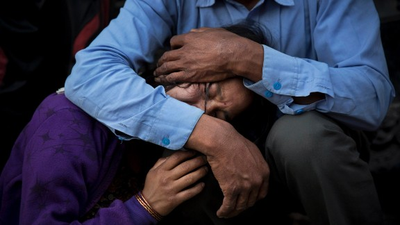 A woman receives comfort during the funeral of her mother, a victim of Nepal