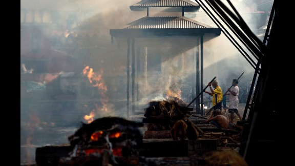 Hindu priests perform rituals during the cremations of victims at the Pashupatinath Temple on the banks of the Bagmati River in Kathmandu on May 1.