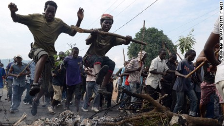 Young Burundians jump over a burning barricade as they demonstrate Friday in Bujumbura,  against the president's bid for a third term.