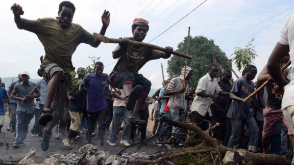 Young Burundians jump over a burning barricade as they demonstrate Friday in Bujumbura,  against the president