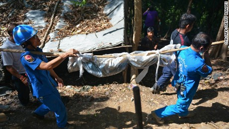 Caption:Rescue workers carry a body uncovered at the site of a mass grave at an abandoned jungle camp in the Sadao district of Thailand's southern Songkhla province bordering Malaysia on May 1, 2015. Authorities in Thailand uncovered a mass grave in an abandoned jungle camp on May 1 believed to contain the remains of migrants from Myanmar and Bangladesh, a grisly find in a region notorious for people smuggling routes. The border area with Malaysia is notorious for its network of secret camps where smuggled migrants are held, usually against their will until relatives pay up hefty ransoms. AFP PHOTO (Photo credit should read STR/AFP/Getty Images)