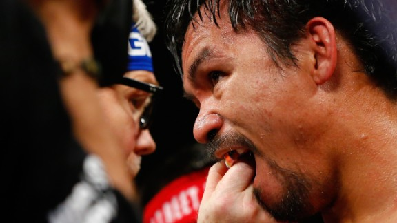 Trainer Freddie Roach adjusts Manny Pacquiao's mouth guard at the MGM Grand Garden Arena in Las Vegas.  .