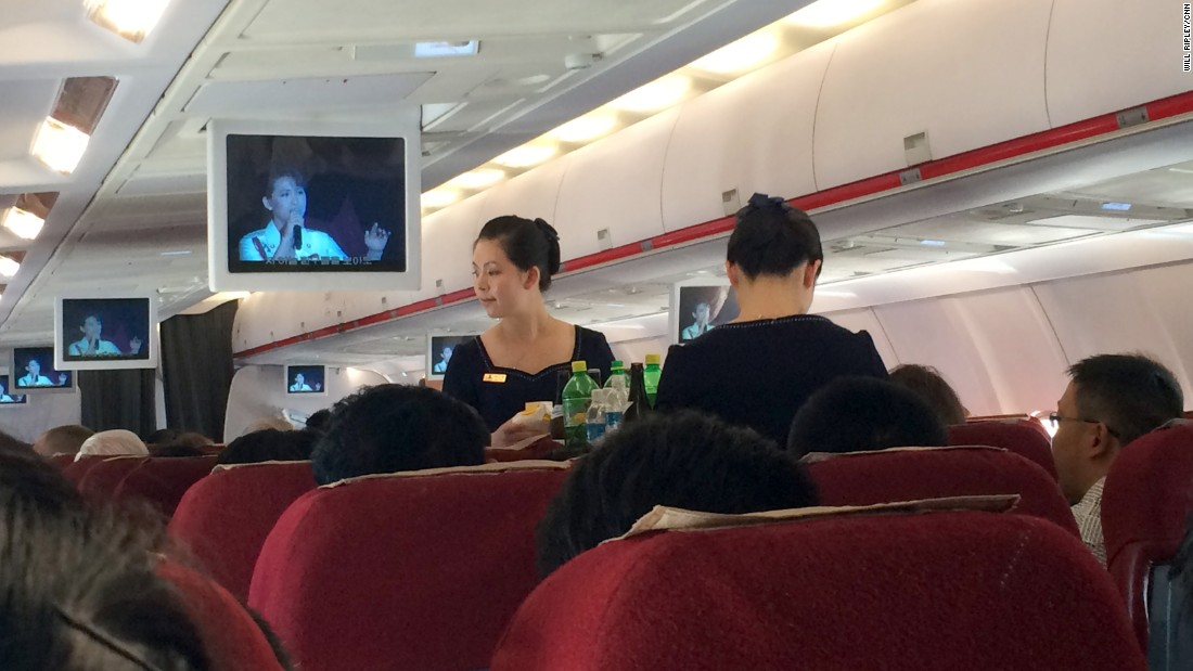 The flight attendants on Air Koryo serve refreshments as monitors show a North Korean televised concert mainly featuring patriotic songs about the military.