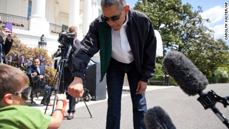 President Barack Obama greets Luca Martinez, 4, with a fist-bump as he walks from the White House to board Marine One.