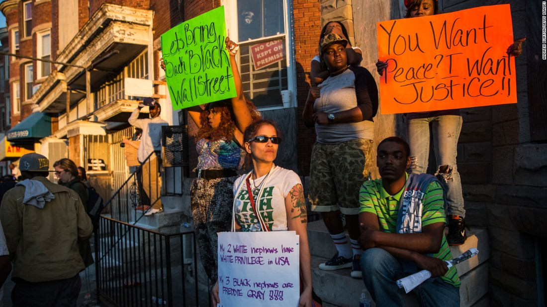 Protesters hold signs on May 2 in the Sandtown neighborhood.