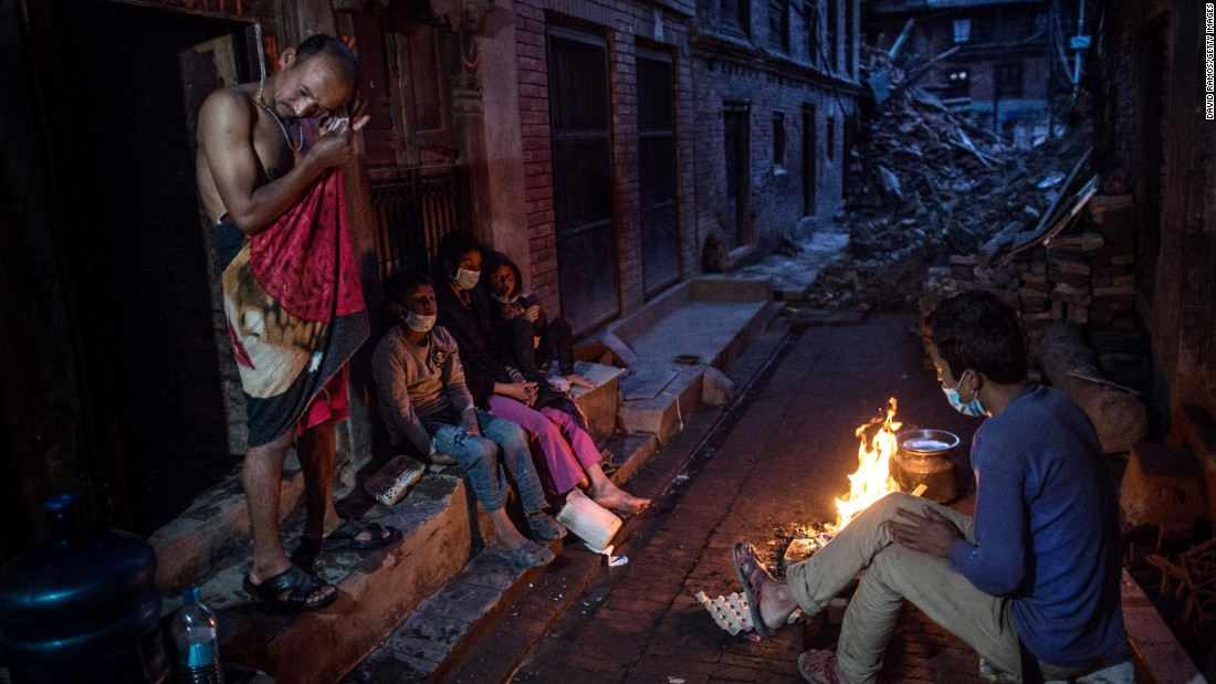 Members of the Tsayana family warm themselves next to a fire outside their damaged house on May 3 in Bhaktapur, Nepal.