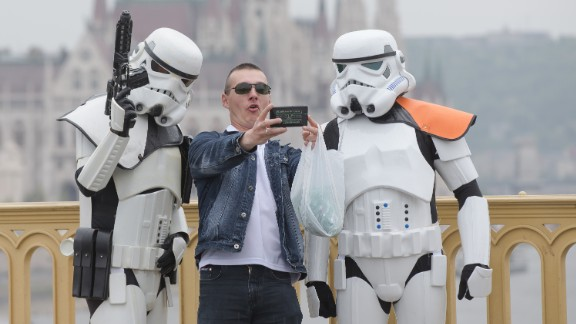 """A man takes a selfie with two """"Star Wars"""" fans dressed as stormtroopers on May 3 in Budapest, Hungary."""