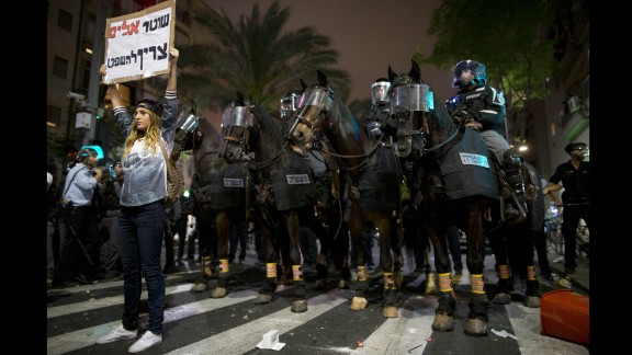 """An Israeli protester holds a sign reading """"violent policemen should be sentenced"""" during clashes between protesters and Israeli riot police in Tel Aviv on Sunday, May 3. The protest was sparked after video emerged showing what appeared to be two police officers beating a uniformed Israeli soldier of Ethiopian origin."""