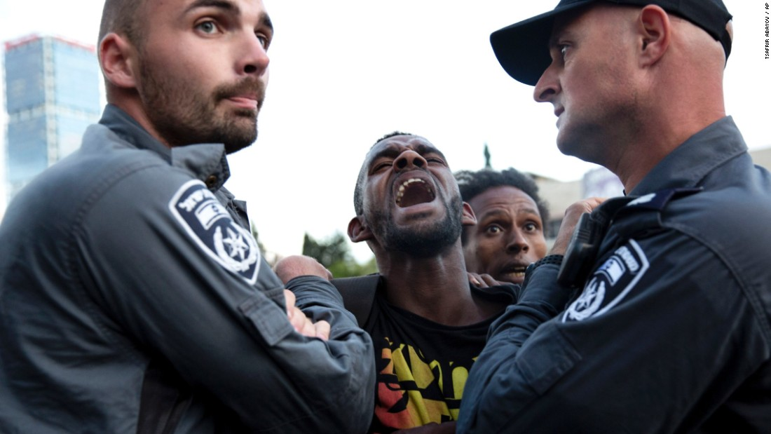 Israeli police officers detain a protester during a demonstration in Tel Aviv on May 3.