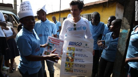 UNICEF Goodwill Ambassador Orlando Bloom carries posters about Ebola prevention, in Liberia.