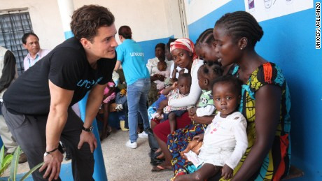 Orlando Bloom speaks with a woman holding her child, at a health center in Monrovia.