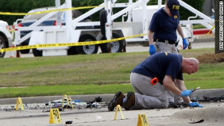 "Investigators work a crime scene before the removal a two bodies outside of the Curtis Culwell Center after a shooting occurred the day before May 04, 2015 in Garland, Texas. During the ""Muhammad Art Exhibit and Cartoon Contest, "" an anti-Islam event, on May 03, Elton Simpson of Phoenix, Arizonia and another man opend fire, wounding a security guard . Police officers shot and killed Simpson at the scene."