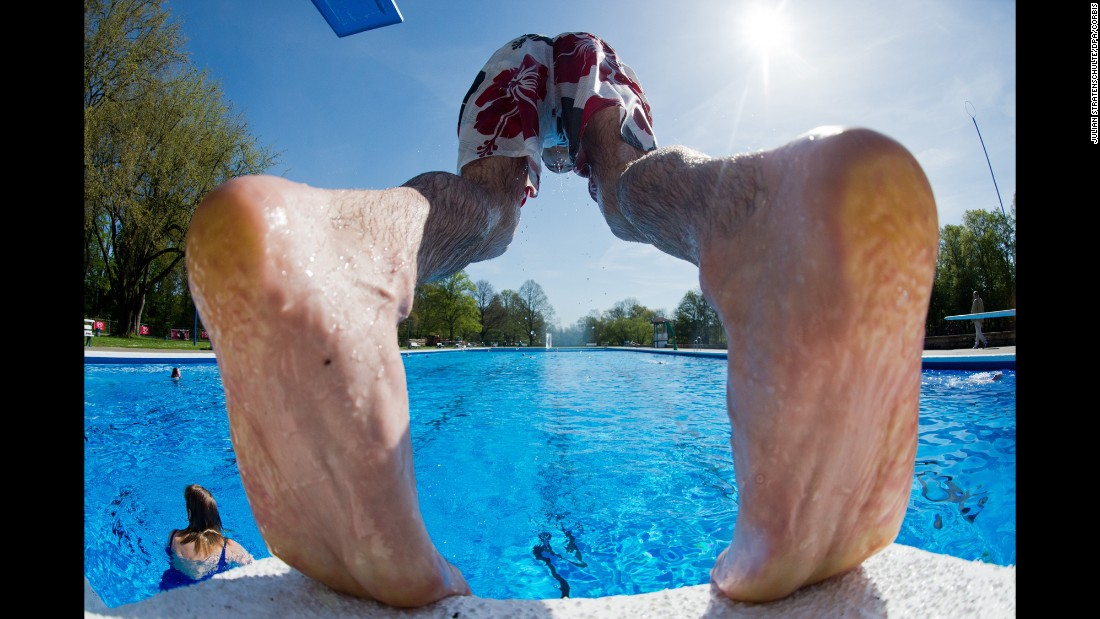 A man dives into the open-air swimming pool in Hanover, Germany, on Wednesday, April 29. <br />