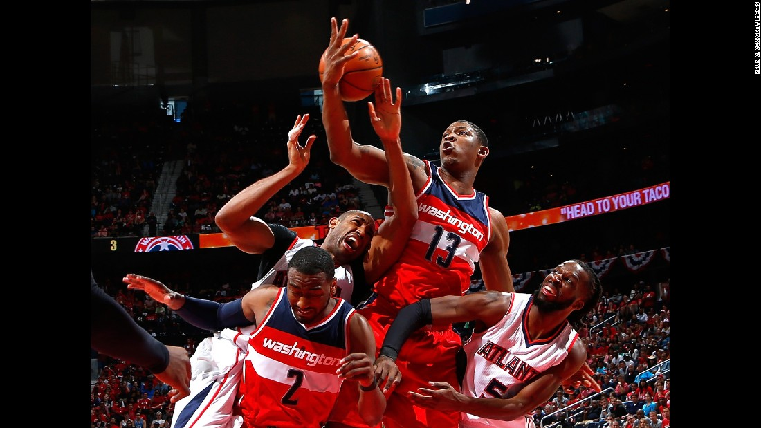 John Wall, lower left, and Kevin Seraphin, middle, of the Washington Wizards defend as Al Horford, left, of the Atlanta Hawks attempts a shot during the 2015 NBA Playoffs on Sunday, May 3, in Atlanta.