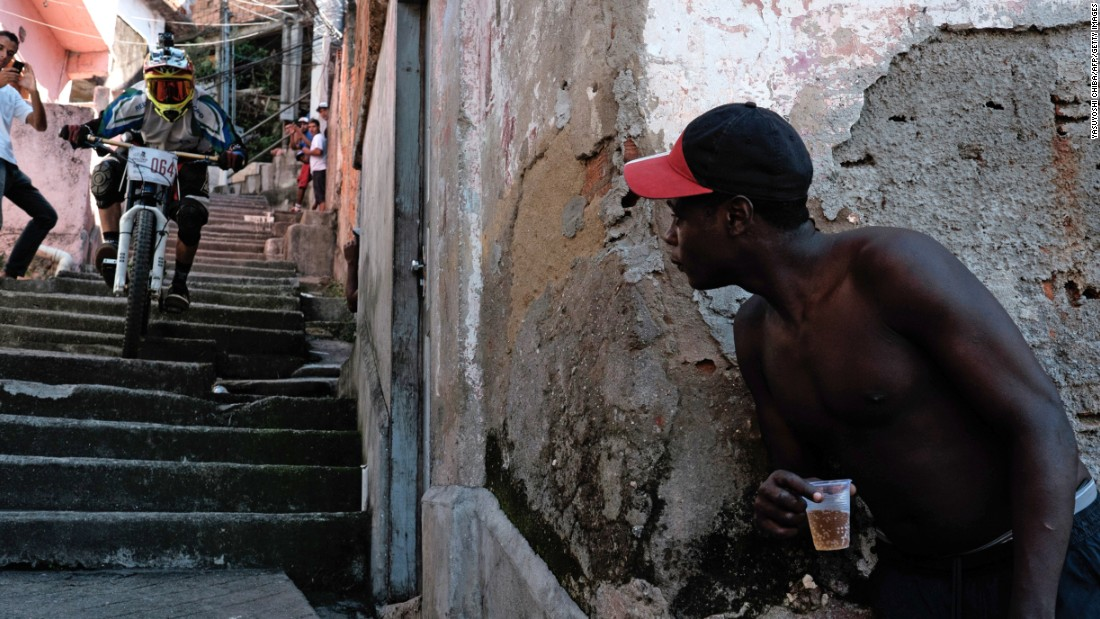 A resident watches a competitor go down the steps of an alley during the Favelas Mountain Bike Circuit at Turano shantytown in Rio de Janeiro on Sunday, May 3. The competition started in March and will be competed in eight stages until November in downhill and cross-country categories.