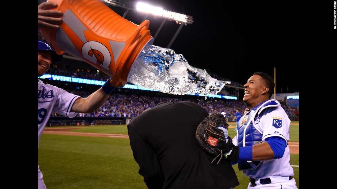 Catcher Salvador Perez, right, of the Kansas City Royals takes cover from teammate Erik Kratz behind broadcaster Joel Goldberg on Friday, May 1, in Kansas City, Missouri.
