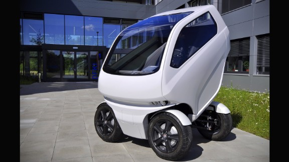 The car reduces its size by partly folding. It shifts the rear axle to the front and slides on a set of rails which raises the cabin upwards.