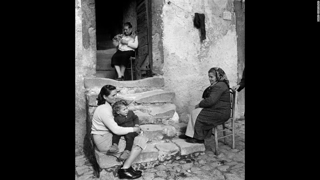 Three generations of women sit and talk on the front steps of a house in Vallecorsa, Italy, in 1968.