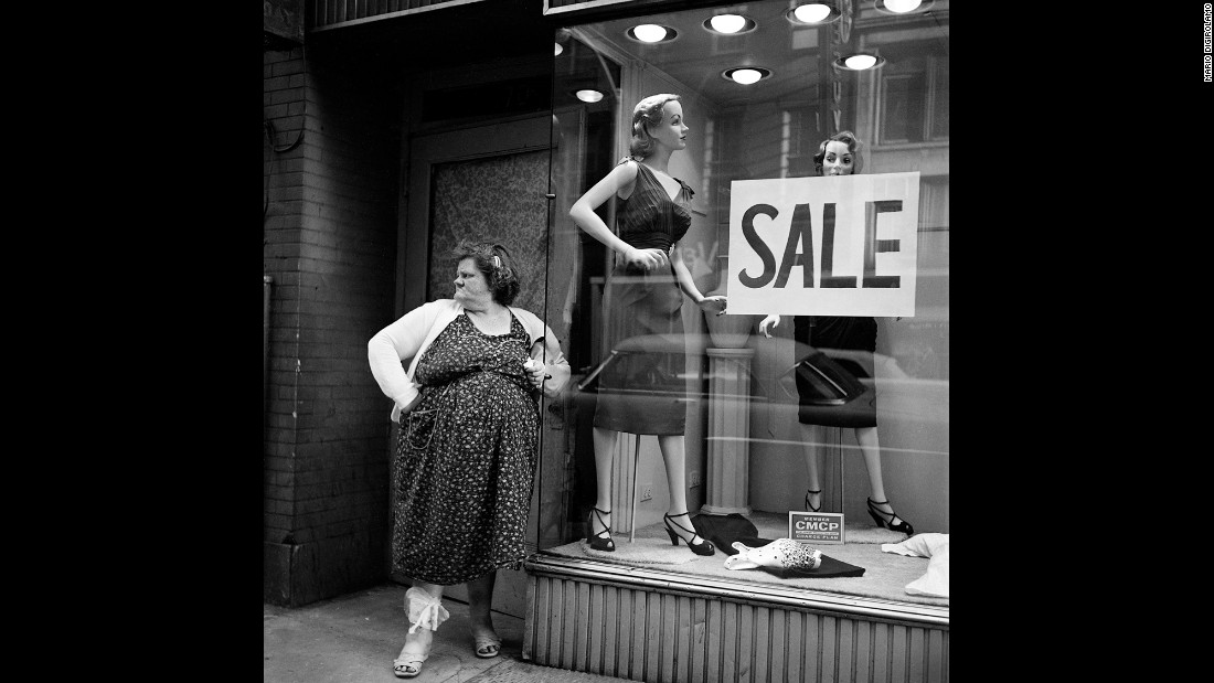 A woman stands in front of a New York store window in 1959. DiGirolamo and his wife traveled together back and forth from New York to Italy, where he was born. He later was a  physician and scientist at Emory University in Atlanta for decades.