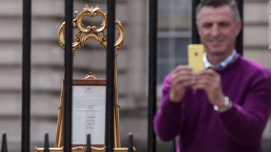 "A man takes a selfie in front of the royal birth announcement of the Duke and Duchess of Cambridge's second child, <a href=""http://www.cnn.com/2015/05/02/world/gallery/royal-baby-princess-announced/index.html"">Princess Charlotte of Cambridge</a>, born on Saturday, May 2."