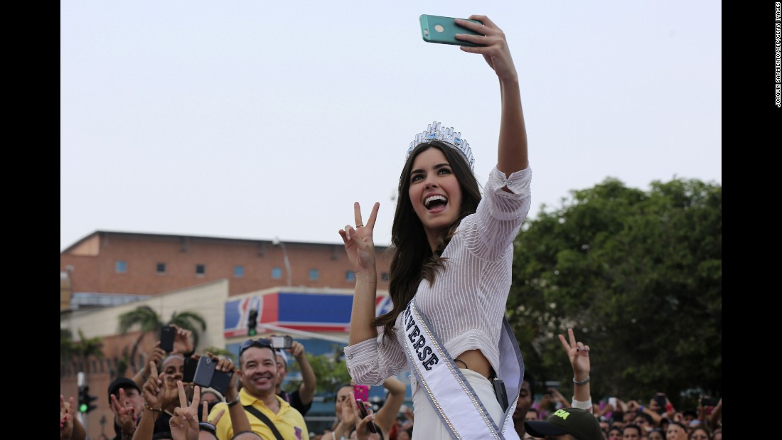 Colombian Miss Universe Paulina Vega Dieppa takes a selfie with a fan's phone during a welcoming event on Friday, on May 1, in her hometown Barranquilla.