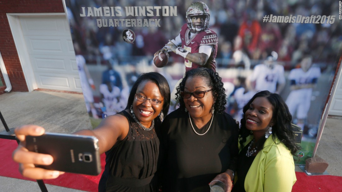 Three women pose for a selfie in Bessemer, Alabama, in front of a Jameis Winston mural at an NFL draft celebration on Thursday, April 30. The quarterback was drafted by the Tampa Bay Buccaneers from Florida State University.